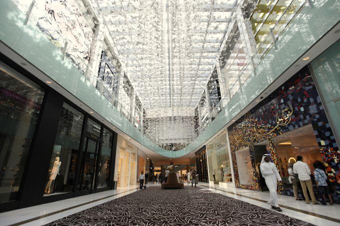 A man walks past a Christian Louboutin store at Dubai Mall shopping center in Dubai