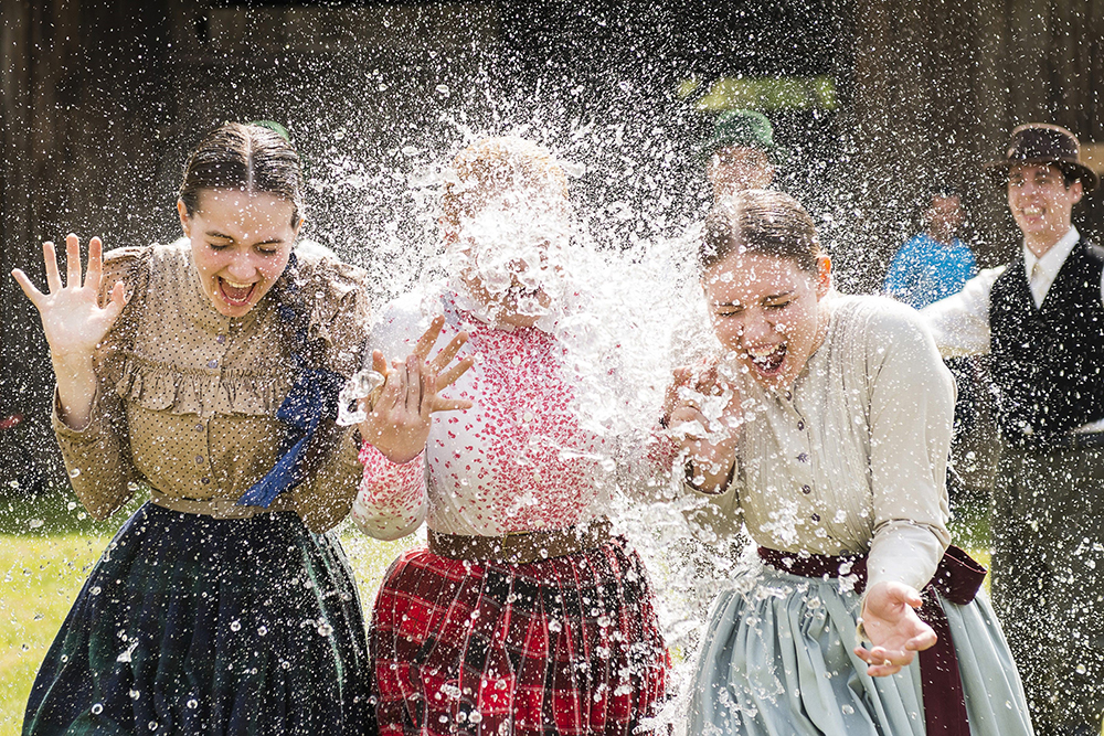 Women in traditional costumes are sprayed with water by men as members of the Marghareta Dance Group perform Easter folk traditions of the region in the Museum Village in Nyiregyhaza, 227 kms northeast of Budapest, Hungary, Monday, April 21, 2014. According to a hundred years old tradition of Hungarian villages, young men pour water on young women who in exchange present their sprinklers with beautifully coloured eggs on Easter Monday. (AP Photo/MTI/ Attila Balazs) ORG XMIT: MTI105