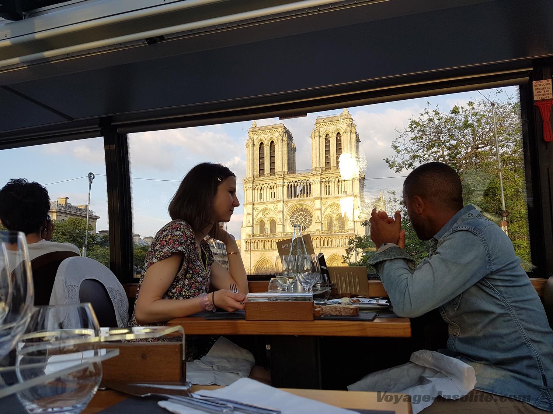 Couple profitant de la vue sur Notre Dame de Paris à bord du bus restaurant, le Bustronome