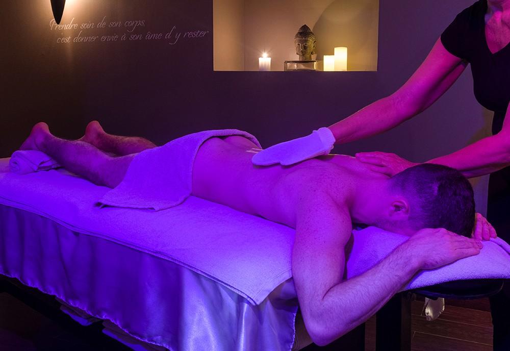 Un homme entrain de se faire masser au spa de Natureva & Spa