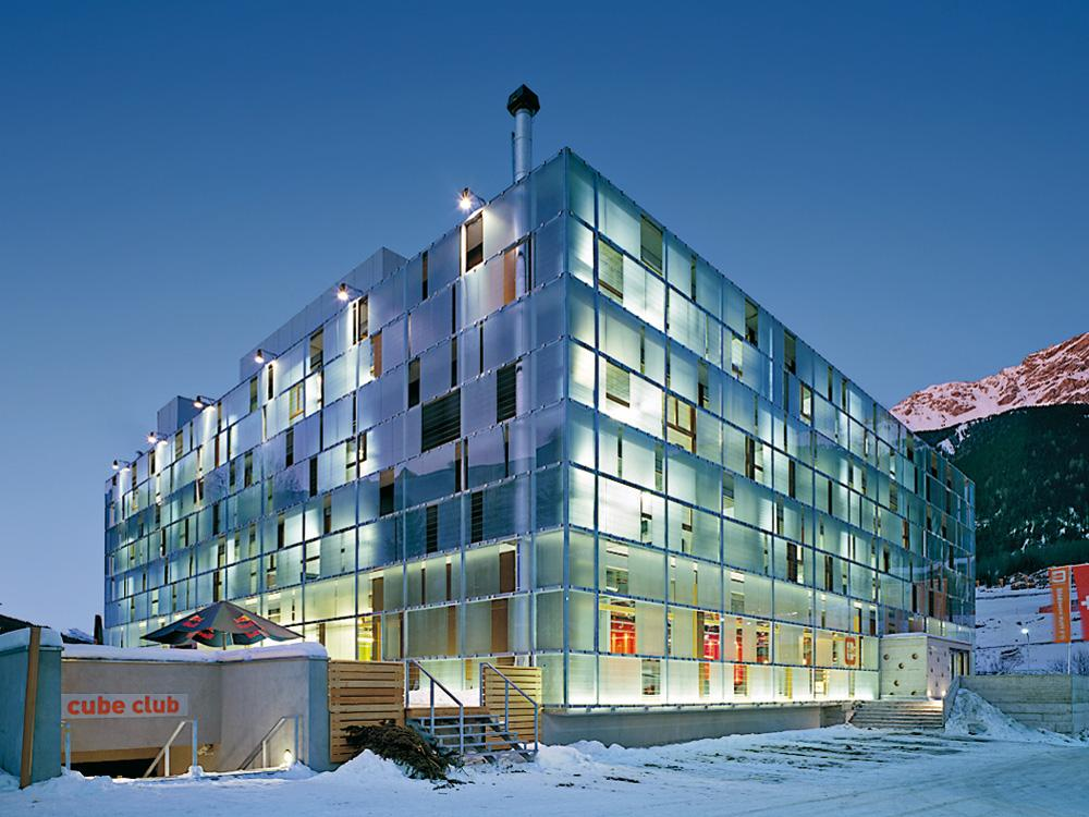 Voici le Cube hôtel Savognin sous la neige en Suisse