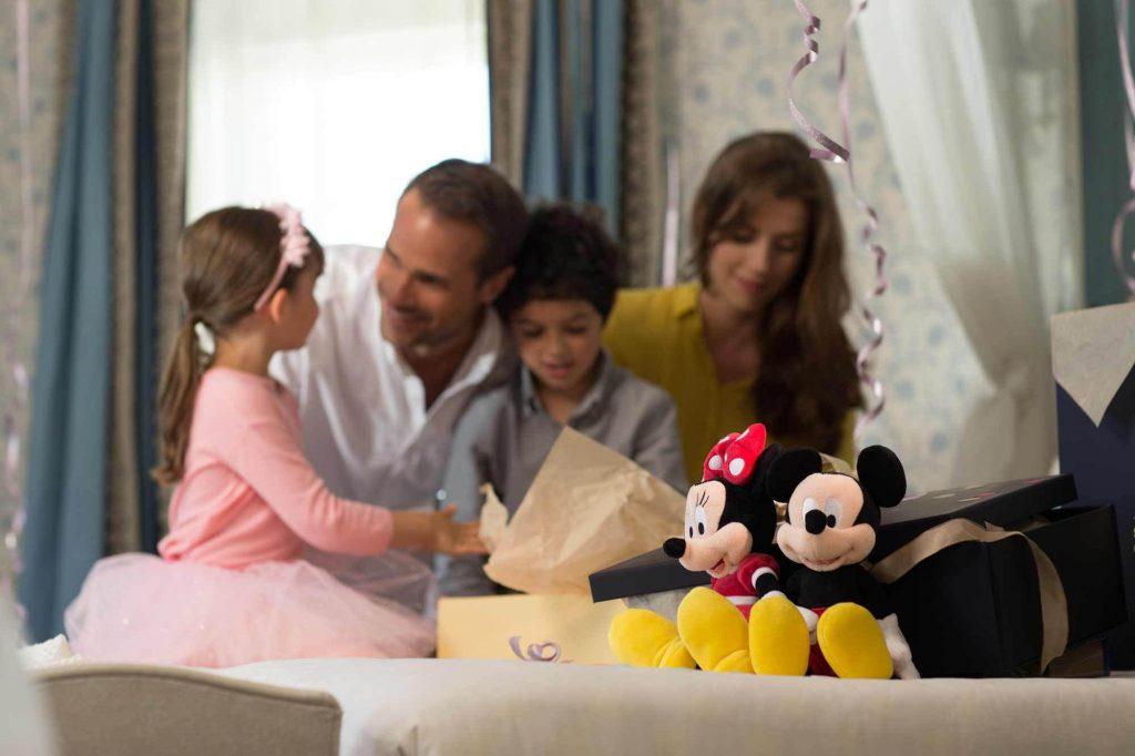 Une famille dans la chambre personnalisée avec des peluches Mikckey et Minnie posés sur le lit