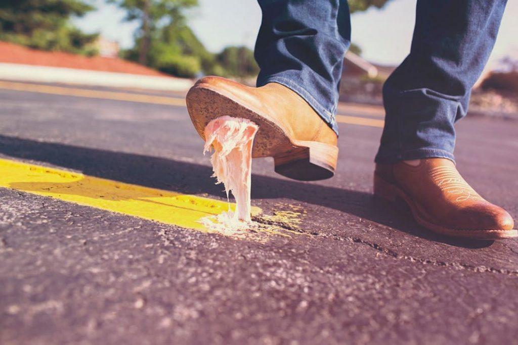 Un chewing-gum collé à la chaussure d'un homme sur la route