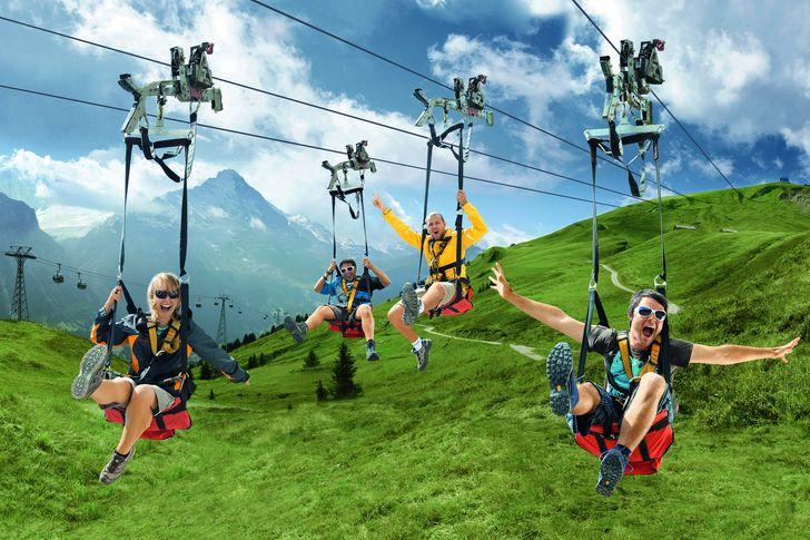 Quatre personnes font de la tyrolienne à la station suisse Gridenwald