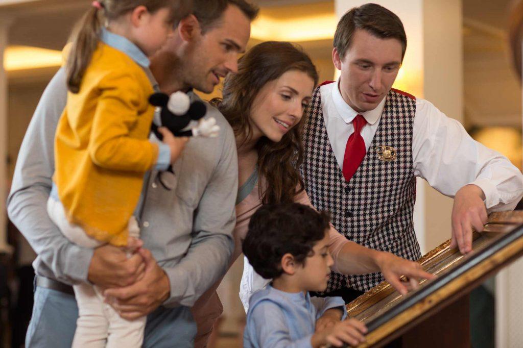 Un personnel qui explique le fonctionnement du mode VIP à une famille