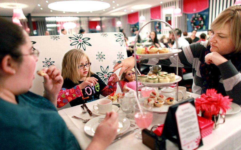 Deux adultes et une petite fille entrain de manger au restaurant American girl