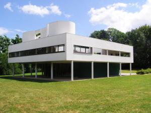Image de la villa Savoye, cube blanc posé sur pilotis sur une grande pelouse arborée.
